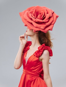 Young beautiful woman in a red dress with a big rose flower