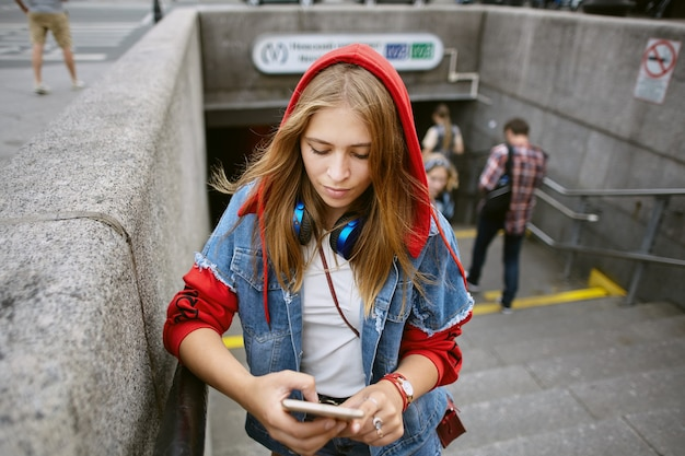Young beautiful woman in red hoodie is standing at entrance of  subway with  mobile phone in hands.