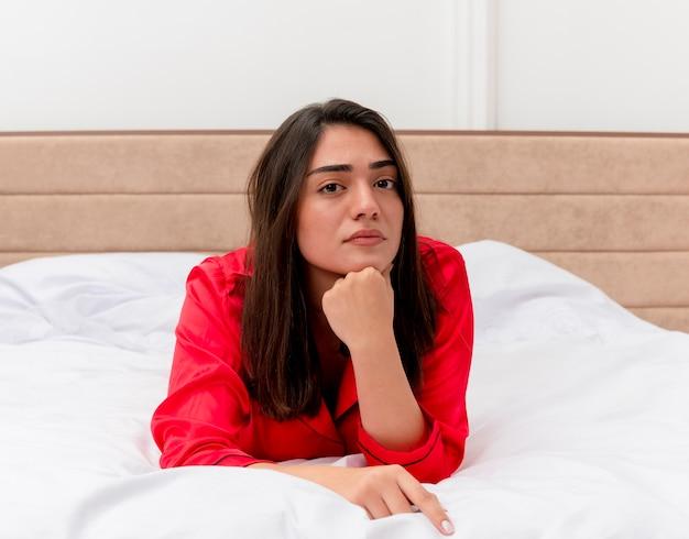 Giovane bella donna in pigiama rosso posa sul letto che guarda l'obbiettivo con espressione pensierosa sul viso pensando in interni domestici su sfondo chiaro