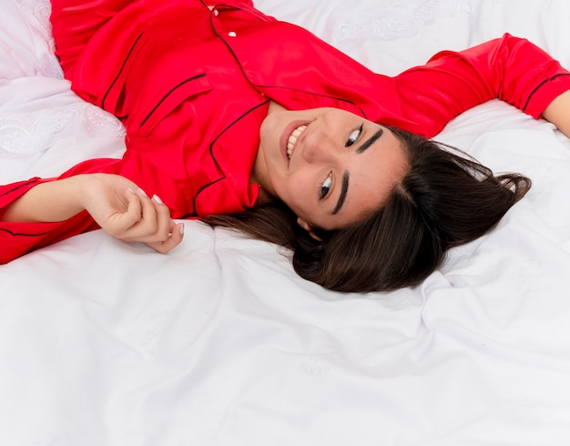 Young beautiful woman in red pajamas laying on bed resting on soft pillows enjoying morning after awakening in bedroom interior on light background