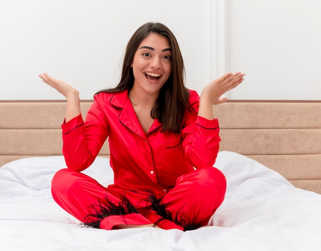 Young beautiful woman in red pajamas sitting on bed looking at camera happy and excited smiling cheerfully in bedroom interior on light background