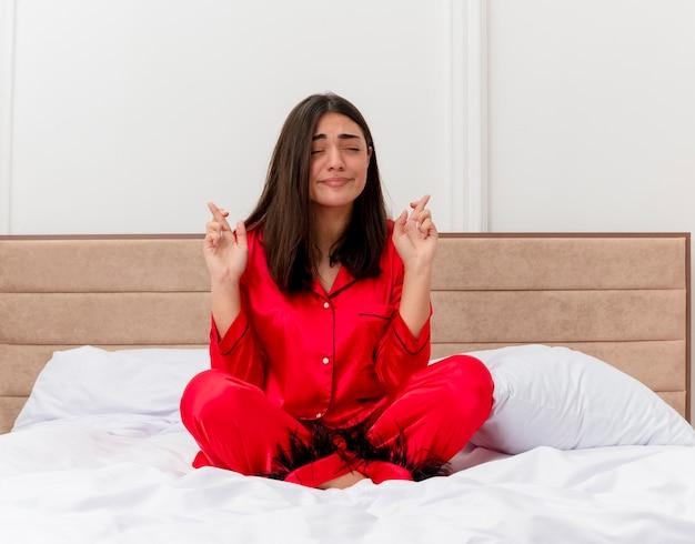 Giovane bella donna in pigiama rosso seduta sul letto che esprime un desiderio desiderabile incrociando le dita con gli occhi chiusi nell'interno della camera da letto