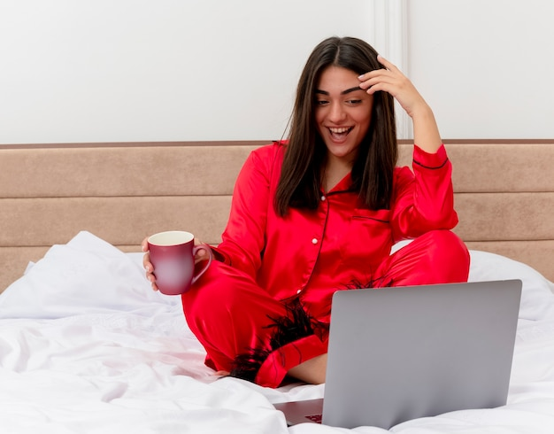 Young beautiful woman in red pajamas sitting on bed with laptop and cup of coffee happy and positive smiling cheerfully in bedroom interior on light background