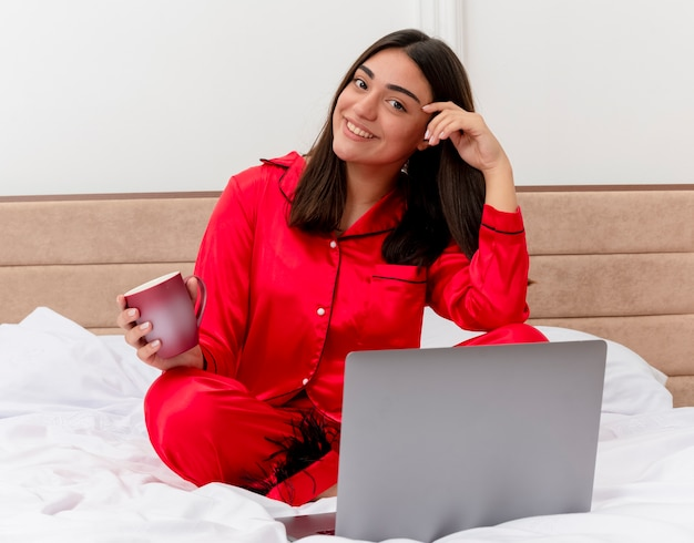 Young beautiful woman in red pajamas sitting on bed with laptop and cup of coffee looking at camera with smile on face happy and positive in bedroom interior on light background