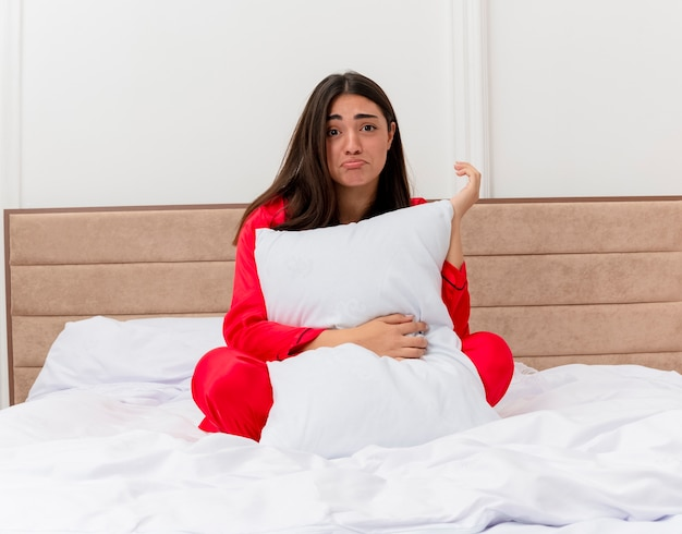 Young beautiful woman in red pajamas sitting in bed with pillow with sad expression in bedroom interior