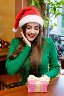 Young beautiful woman in red santa claus hat looking at gift box in cafe