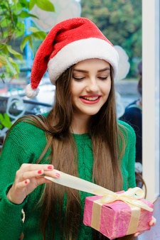 Young beautiful woman in red santa claus hat opening a gift box