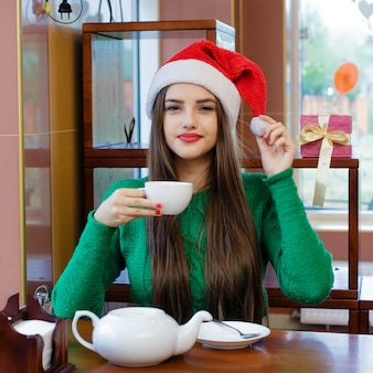 Young beautiful woman in red santas hat drinking tea in cafe
