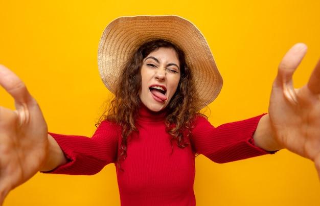Giovane bella donna in dolcevita rosso con cappello estivo felice e allegra che si diverte a tirare fuori la lingua in piedi sull'arancia