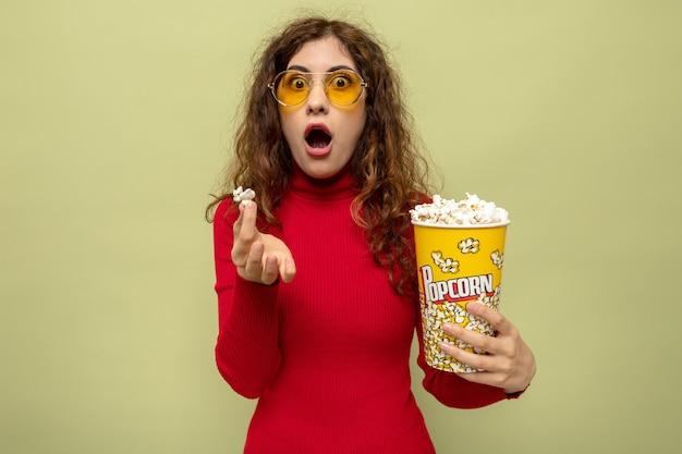 Giovane bella donna in dolcevita rosso che indossa occhiali gialli con secchio di popcorn stupito e sorpreso in piedi sul verde
