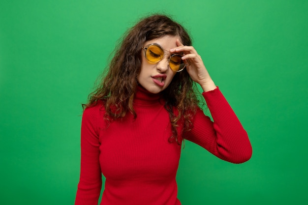 Young beautiful woman in red turtleneck wearing yellow glasses looking aside with hand on her head making wry mouth with disappointed expression standing over green wall