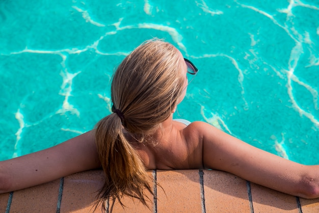 A young beautiful woman relaxes at the swimming pool. wellness concept. spa and relax, woman happiness.