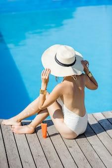 木製のプールサイドで日焼け止めローションと一緒に座って盆地でリラックスした若い美しい女性。日焼け止めソーラークリームuv保護コンセプト