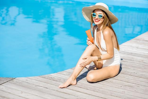 木製のプールサイドで日焼け止めローションと一緒に座っている盆地でリラックスした若い美しい女性。日焼け止めソーラークリームuv保護コンセプト