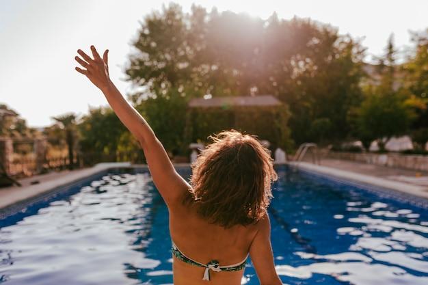 夕暮れ時のスイミングプールでリラックスした若い美しい女性。背面図