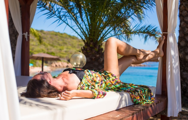 Young beautiful woman relaxing on beach bed during tropical vacation