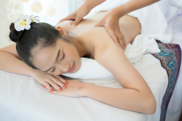 Young beautiful woman relaxing during massage in spa salon.