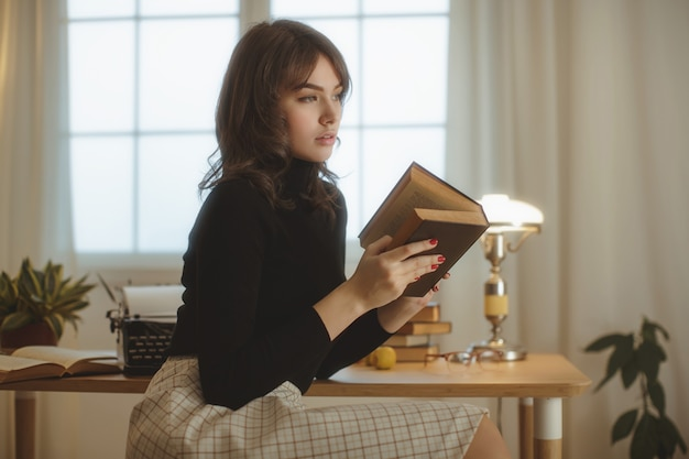 Young beautiful woman relaxing at home in the cozy evening and reading book.