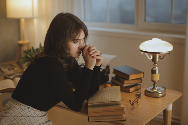 Young beautiful woman relaxing at home in the cozy evening and reading book