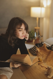 Young beautiful woman relaxing at home with cat in the cozy evening and reading book.
