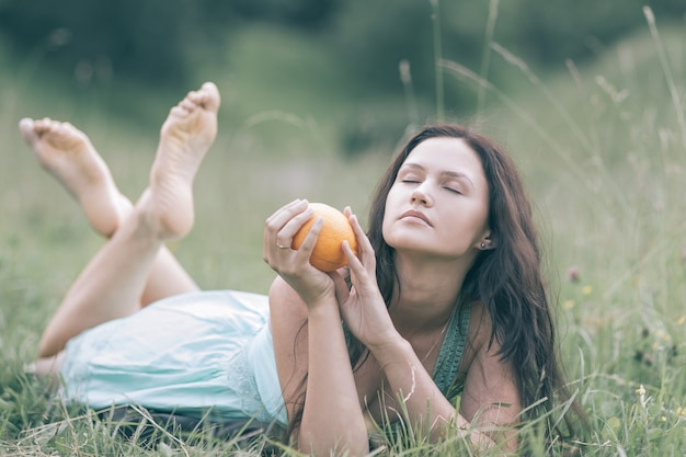 Young beautiful woman relaxing on the lawn on a summer day