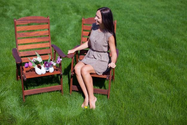 Молодая красивая женщина отдыхает и веселится во дворе