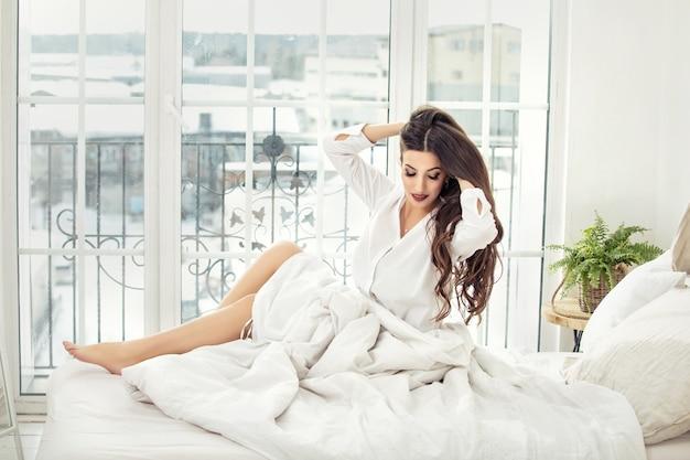 朝の白いシャツの寝室で自宅で休んでいる若い美しい女性