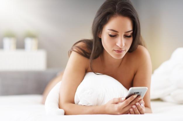 スマートフォンでベッドで休んでいる若い美しい女性