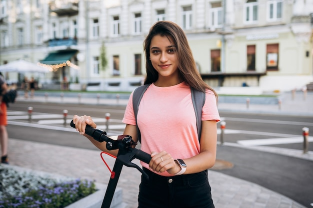 Giovane bella donna che guida uno scooter elettrico, ragazza moderna sul trasporto ecologico.