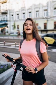 Giovane bella donna in sella a uno scooter elettrico, ragazza moderna sul trasporto ecologico.