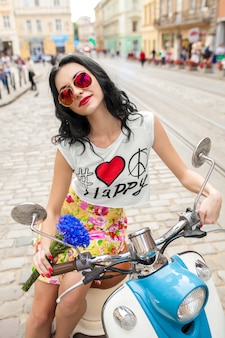 Giovane bella donna a cavallo sulla strada della città di moto