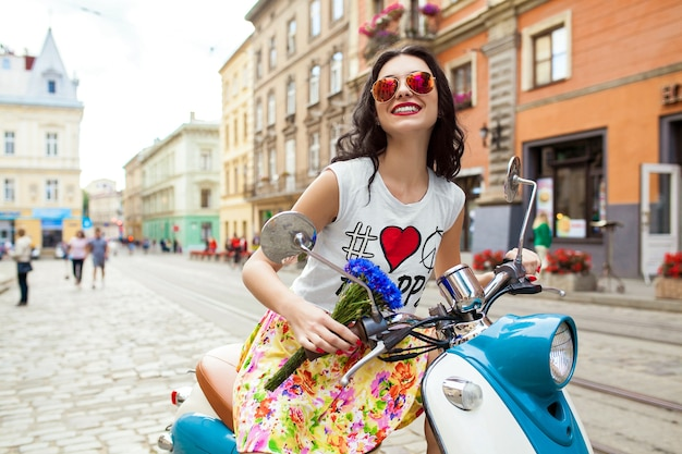 Young beautiful woman riding on motorbike city street
