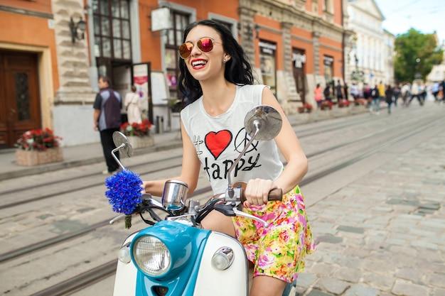 Молодая красивая женщина, езда на мотоцикле городской улице