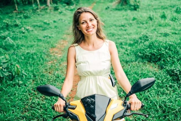 ヤシの木と道路でスクーターに乗って若い美しい女性。熱帯旅行のコンセプト