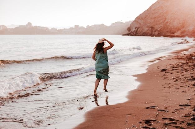 夕暮れ時のビーチで走っている若い美しい女性