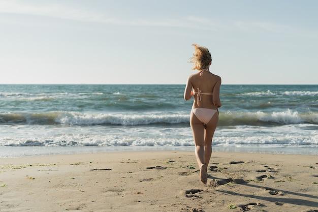 Young beautiful woman runs to the ocean