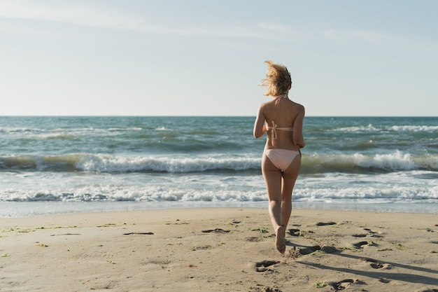 Молодая красивая женщина бежит к океану