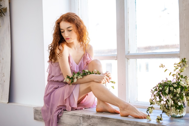 Young beautiful woman sad by the window