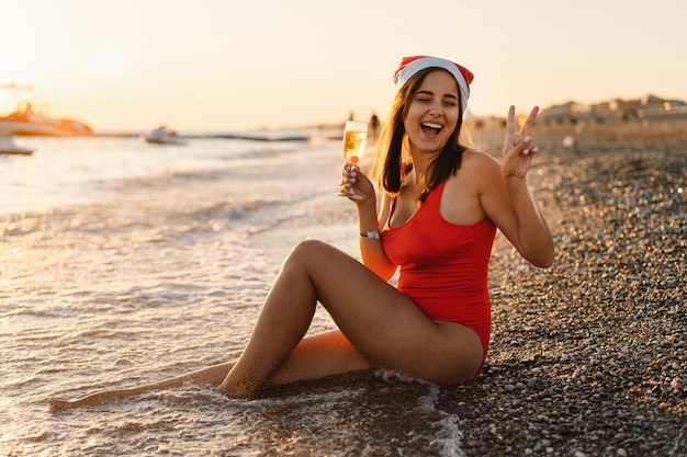 Young beautiful woman in a santa hat with a glass of champagne in her hands walk on the beach