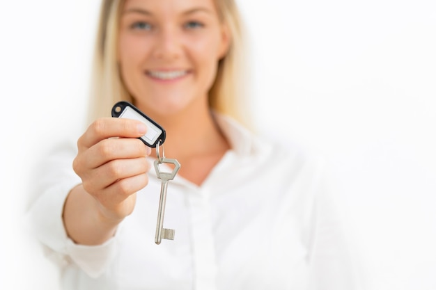 Young beautiful woman showing apartment keys on white. real estate concept.
