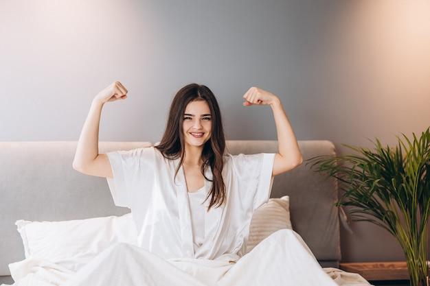 彼女の上腕二頭筋を示す若い美しい女性。女性がベッドで朝の運動をしています。スポーツと健康的なライフスタイル。