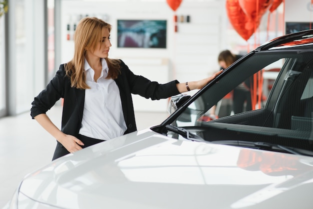 Young beautiful woman showing her love to a car in a car showroom