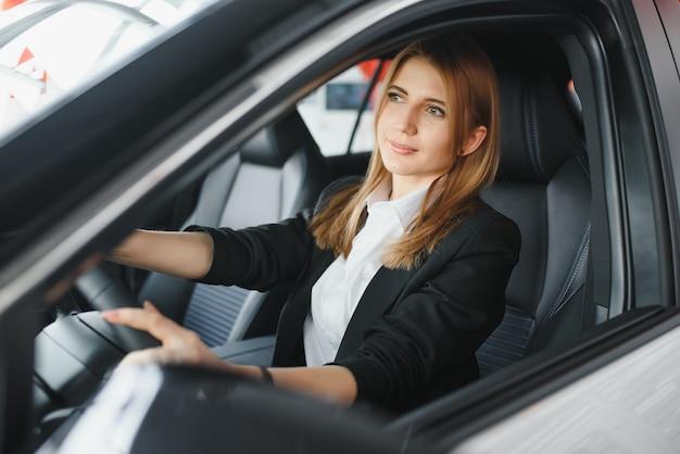 자동차 쇼룸에서 차에 그녀의 사랑을 보여주는 젊은 아름 다운 여자