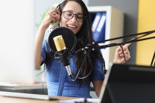 스튜디오에서 노래를 녹음하는 헤드폰으로 마이크에 노래하는 젊은 아름다운 여성