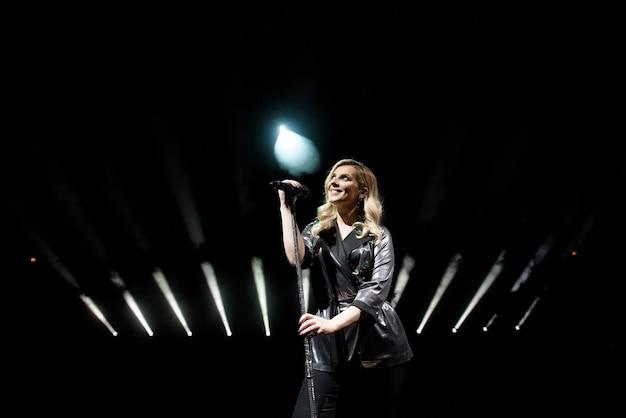 Young beautiful woman singing in whitel smoke, close up.