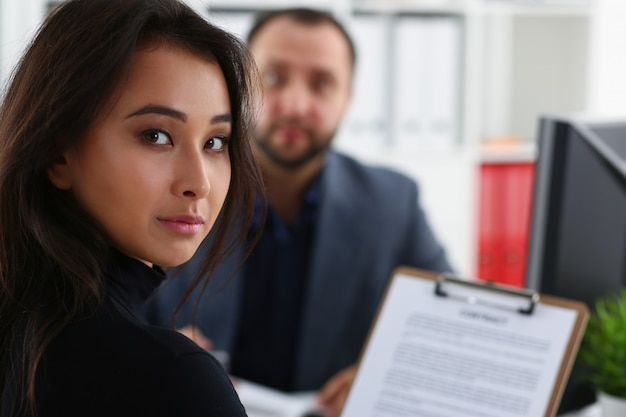 Young beautiful woman sit on chair at table in office in cabinet of her boss hold binder in arms