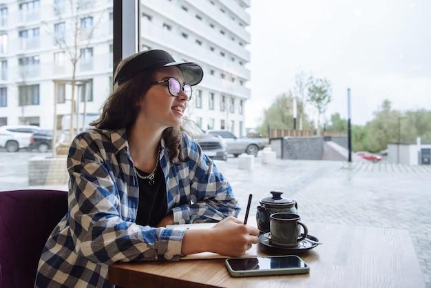 젊고 아름다운 여성이 레스토랑의 테이블에 앉아 양동이에 글을 씁니다.