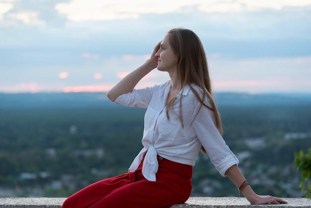 아름다운 젊은 여성은 탁 트인 플랫폼에 앉아 손으로 머리를 곧게 펴고 있습니다. 세련 된 여자의 초상화입니다.