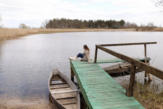 春の日に川の上の木製の橋に座っている若い美しい女性。海岸近くの古いボート。セレクティブフォーカス。