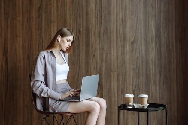 앉아서 인터넷을 사용하여 노트북 작업을 하는 젊은 아름다운 여성